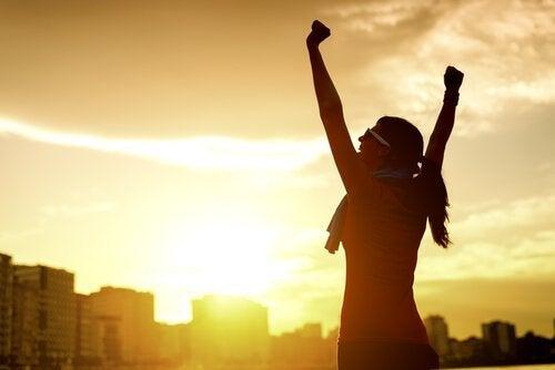 Ciekawość - Szczęśliwa kobieta podnosi ręce do góry