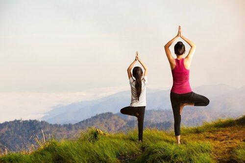Matka z córką robią jogę na wzgórzu