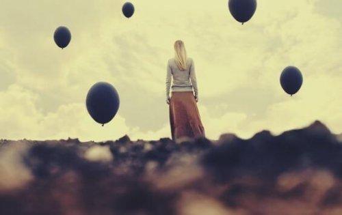 Stojąca dziewczyna i czarne balony w powietrzu