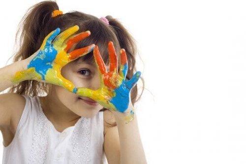 Dziewczynka z rękami kolorowymi od farby