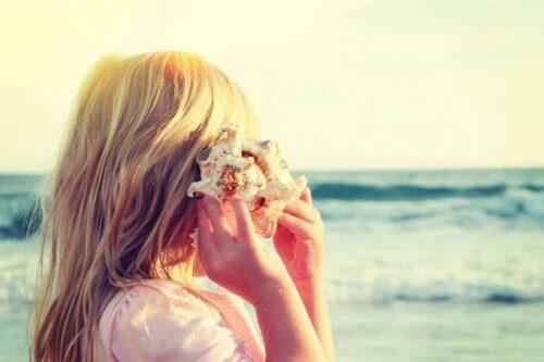 dziewczynka słuchająca muszli