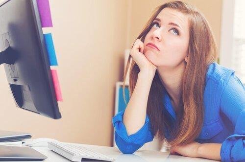 Znudzona kobieta w biurze przy komputerze