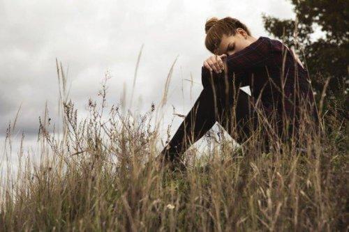 Smutna kobieta siedząca na ziemi