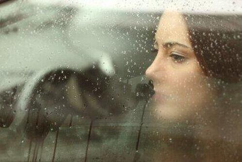 Kobieta przy oknie w deszczu