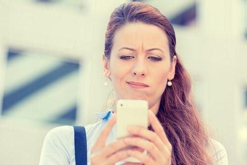 Kobieta ze zdziwioną miną patrzy na telefon