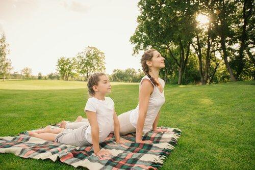 Joga - Matka z córką leżą na trawie
