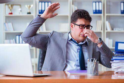 Mężczyzna w biurze zakrywa swój nos
