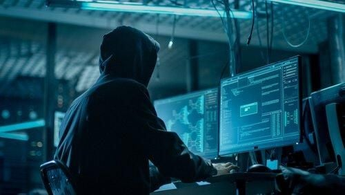 Mężczyzna w kapturze korzysta z komputera
