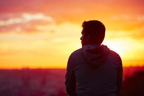 Mężczyzna stojący tyłem na tle zachodzącego słońca