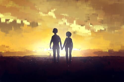 Para trzymająca się za ręce idzie ku zachodowi słońca