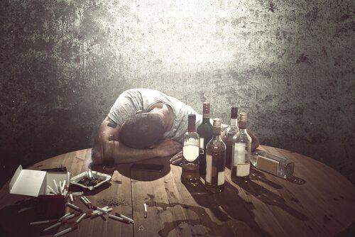Pijany mężczyzna i alkohol na stole
