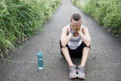 Syndrom przetrenowania - załamany biegacz siedzi na drodze