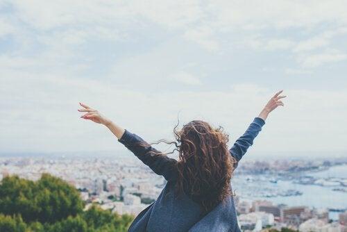 Szczęśliwa dziewczyna z rękami w górze