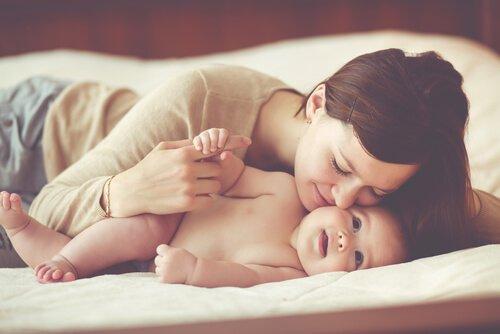 Szczęśliwa mama całuje niemowlę - macierzyństwo