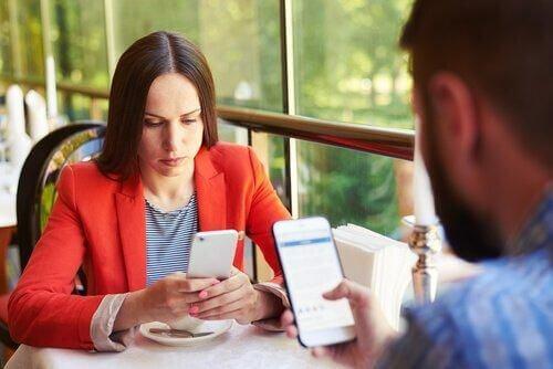 Uzależnienie od telefonu - para na spotkaniu korzysta z telefonów