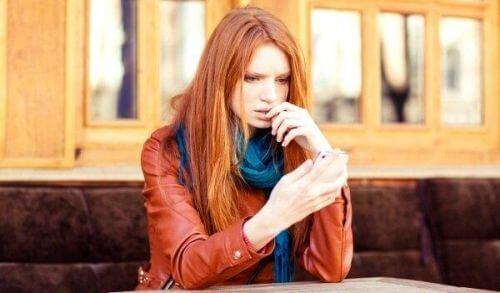Zestresowana kobieta patrzy na telefon
