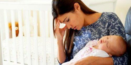 Zmęczona matka trzyma na rękach śpiące dziecko - macierzyństwo