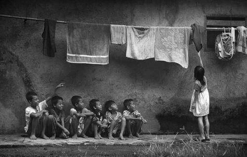Chłopcy patrzą jak dziewczyna wiesza pranie - dehumanizacja w społeczeństwie