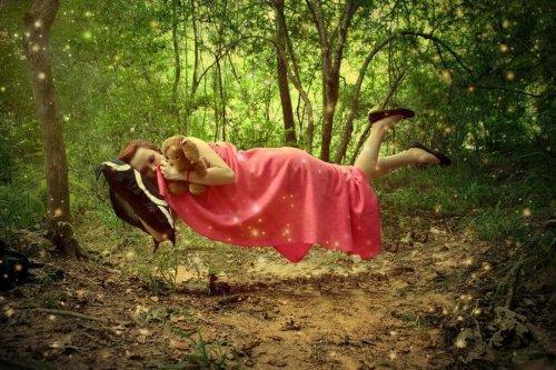 Dziewczyna unosi się w powietrzu w lesie