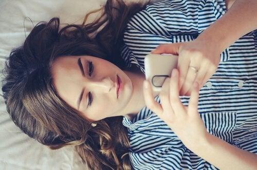 Dziewczyna leżąca na łóżku z telefonem w dłoniach - czy to uzależnienie od WhatsApp?