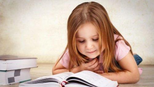 Mała dziewczynka czyta książkę leżąc na podłodze