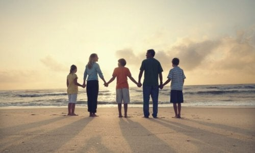 Rodzina na plaży trzyma się za ręce poprawiając klimat emocjonalny