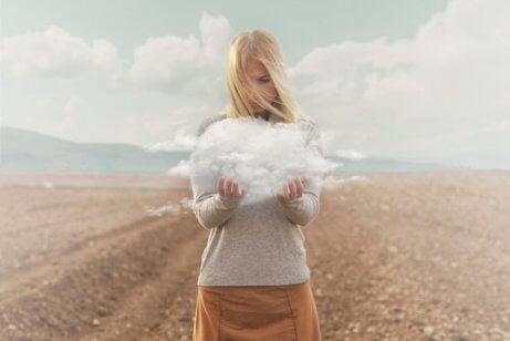 Kobieta trzyma w dłoniach chmurę