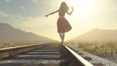 Kobieta idzie wzdłuż torów kolejowych