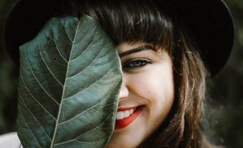 Kobieta ukrywa za liściem pół twarzy z uśmiechem Duchenn'a