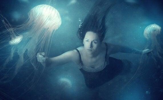 Kobieta pływająca z meduzami