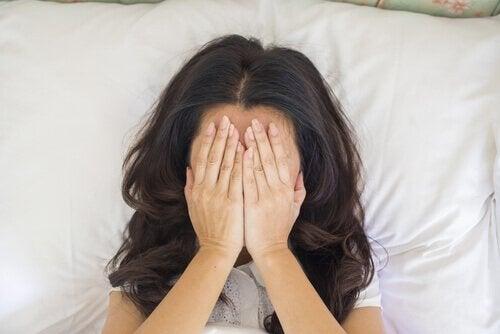 Kobieta na łóżku zasłania twarz rękoma