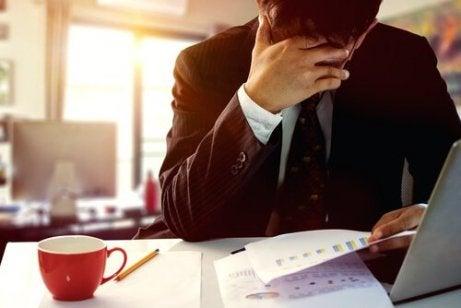 Mężczyzna podpiera głowę ręką siedząc za biurkiem