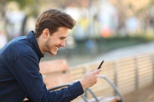 Mężczyzna uśmiechający się do telefonu