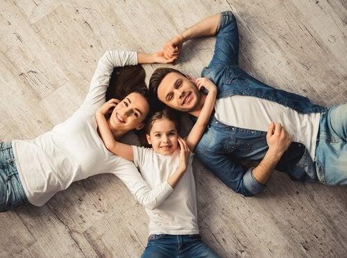 Rodzice z dzieckiem leżą na podłodze