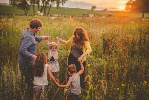 Rodzice i trójka dzieci trzymają za ręce na łące