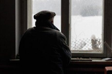 Starzec wpatruje się w okno