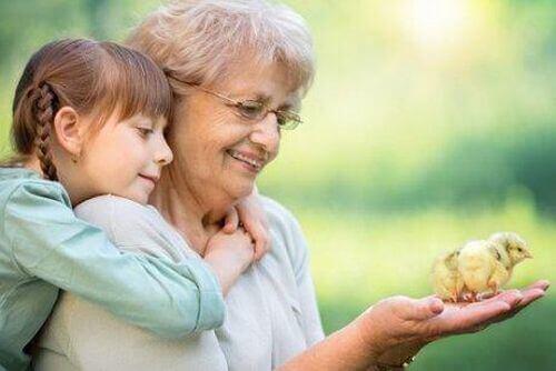 Babcia i wnuczka trzymają pisklę