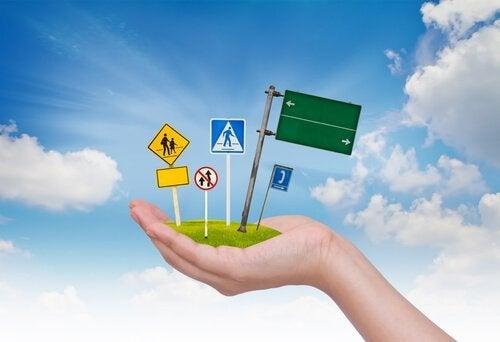 Dłoń trzymająca znaki drogowe