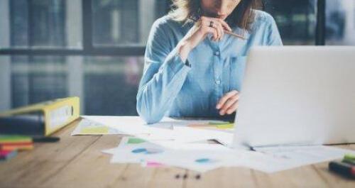 Kobieta pracuje za biurkiem przy komputerze