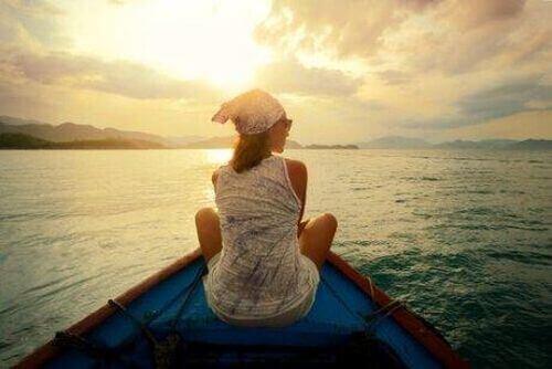 Kobieta siedzi na łódce na środku oceanu