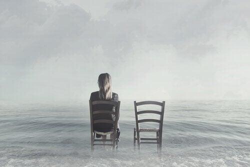 Kobieta siedzi na krześle nad morzem