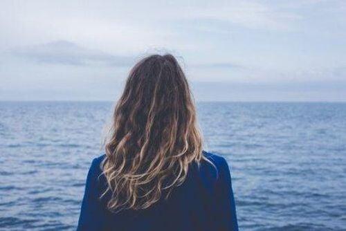 kobieta stoi tyłem i patrzy na ocean