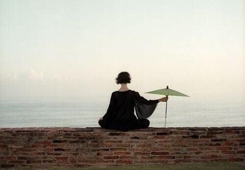 kobieta z parasolką patrząca na morze