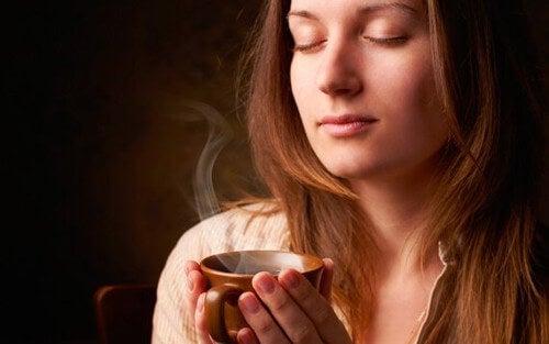 Kobieta wdycha zapach kawy.