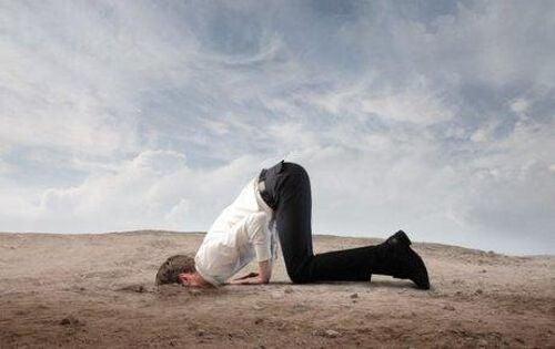 Mężczyzna chowa głowę w piasek jak struś