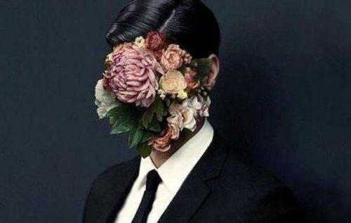 Mężczyzna z kwiatami zakrywającymi twarz