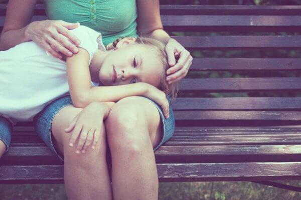 Rodzina niepełna - smutna dziewczynka na kolanach matki
