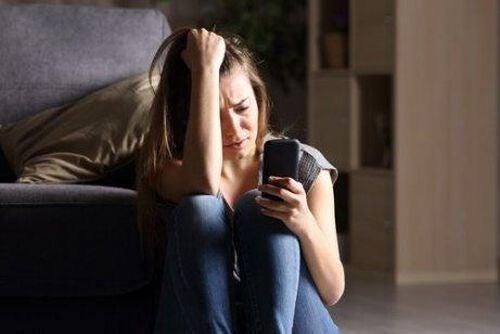 Zestresowana kobieta patrzy na telefon komórkowy