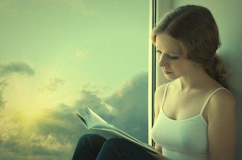 kobieta czytająca książkę przy oknie