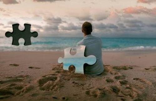 Mężczyzna na plaży z prakującymi puzzlami